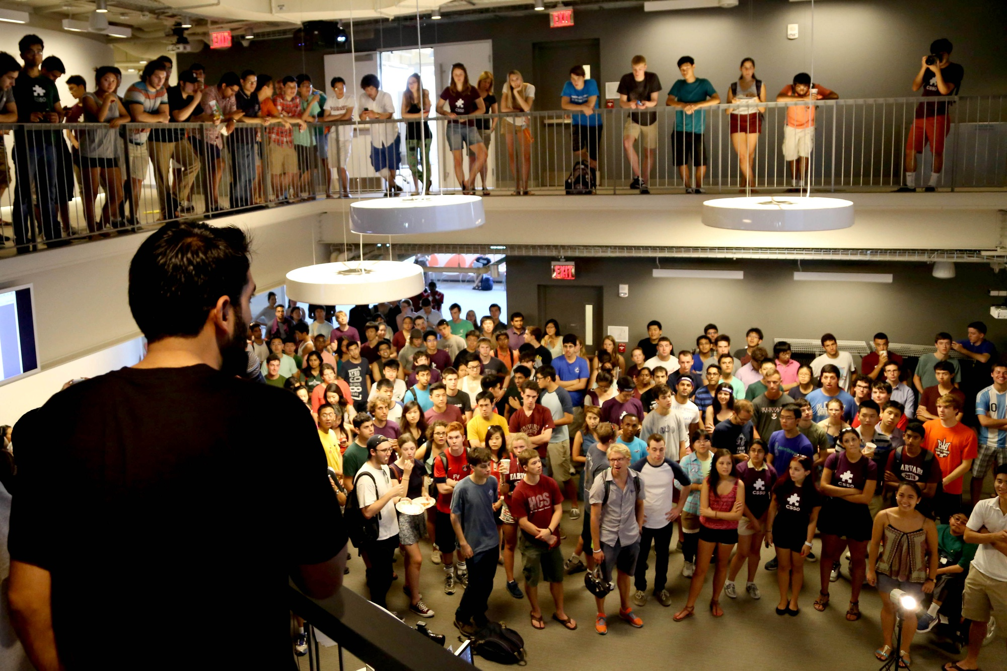 """Mohammed N. Oosman, a university recruiter for Facebook, welcomes the crowd at CS50 Puzzle Day. Malan has described """"a mutually beneficial relationship"""" between CS50 and tech companies."""