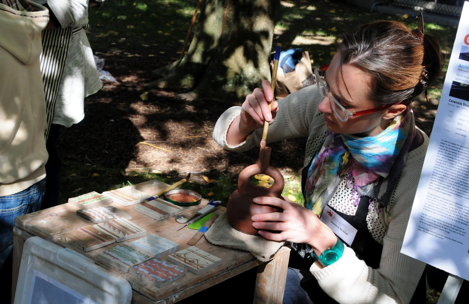 OFA Artist-in-Residence Jessica A. Brandl touches up a clay vessel at the archaeology fair was held by the Peabody Museum and the Semitic Museum on Oct. 5.