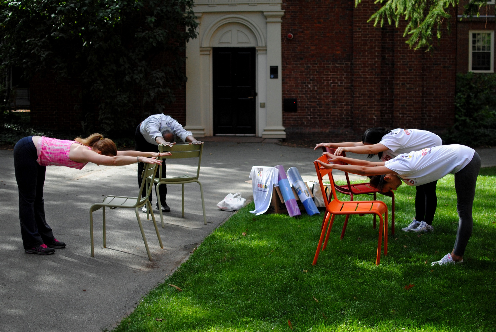 Members of the Harvard Community do yoga outside Holden Chapel in Harvard Yard on Wednesday. The event was a part of the Mind, Body, and Spirit series hosted by the OSL Equity, Diversity and Inclusion Offices.