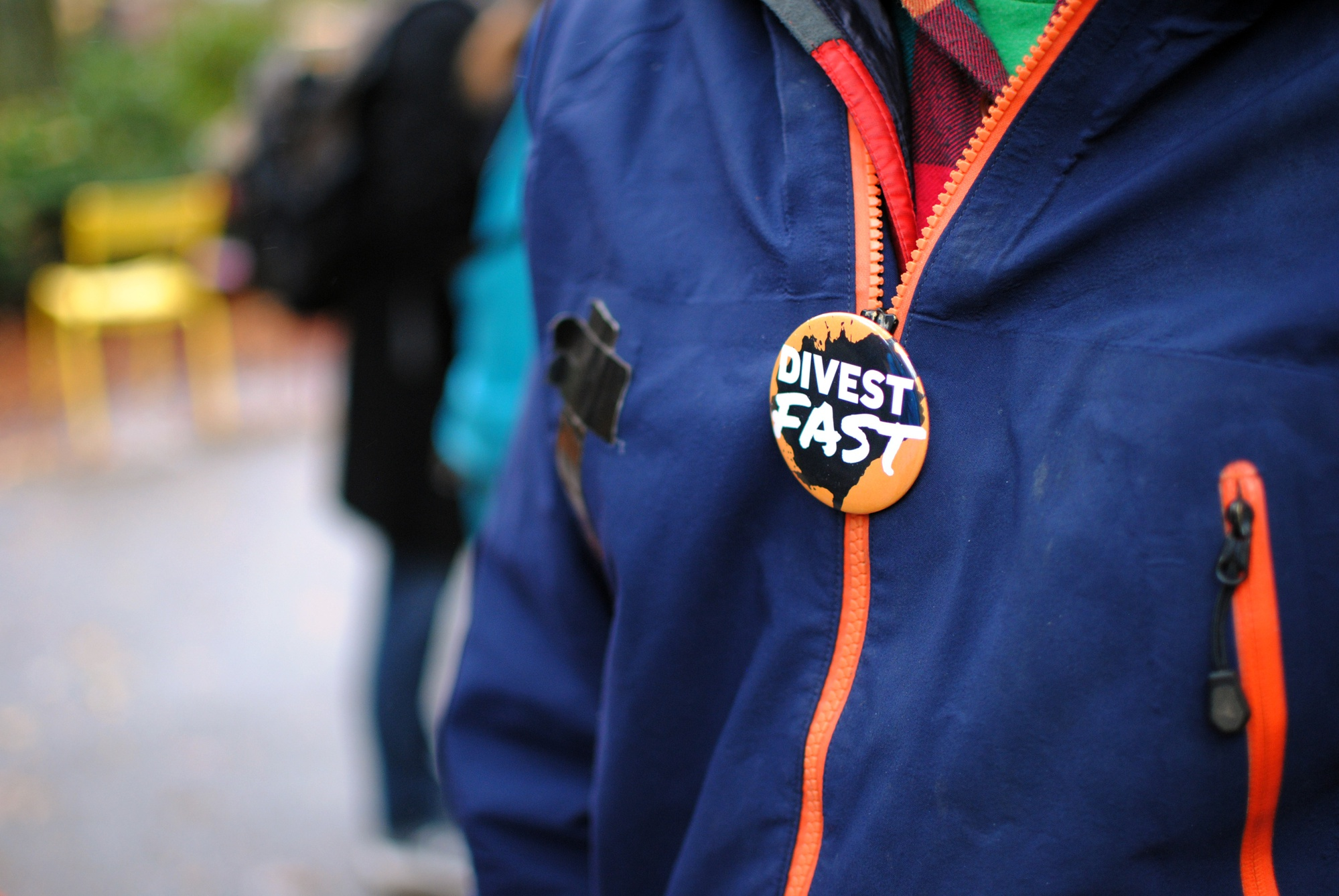 Henney Sullivan '15 dons a 'Divest Fast' pin at the Divest Harvard tent outside Massachusetts Hall in Harvard Yard on Wednesday. Sullivan is one of many students participating in the fast for fossil fuel divestment; he has not eaten since Sunday.