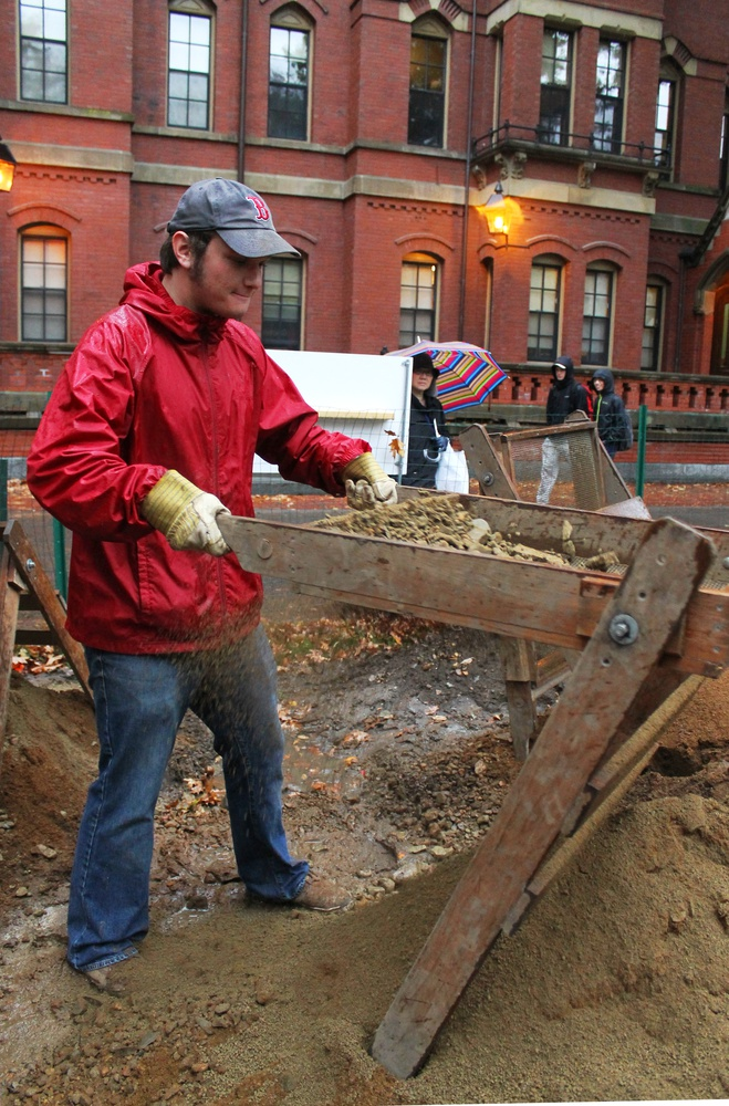 Students of the Harvard Yard Archaeology Project sift through excavation finds on Thursday at the Results Day outside of Matthews Hall.