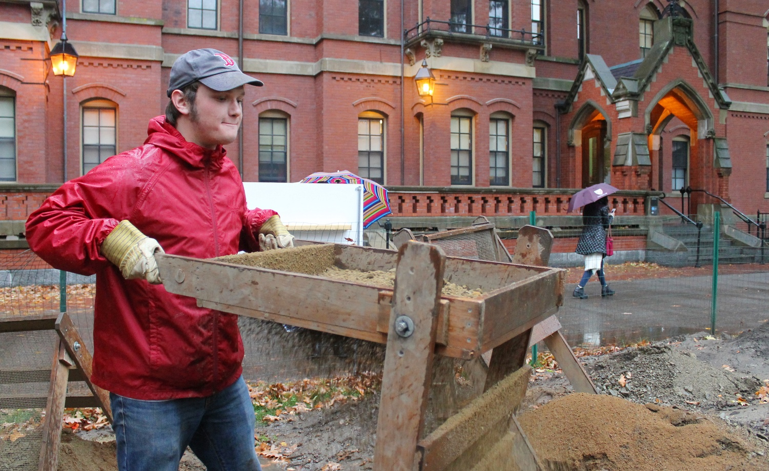 A student sifts through excavation finds of the predicted site of the Indian College on Thursday at the results day outside of Matthews Hall.