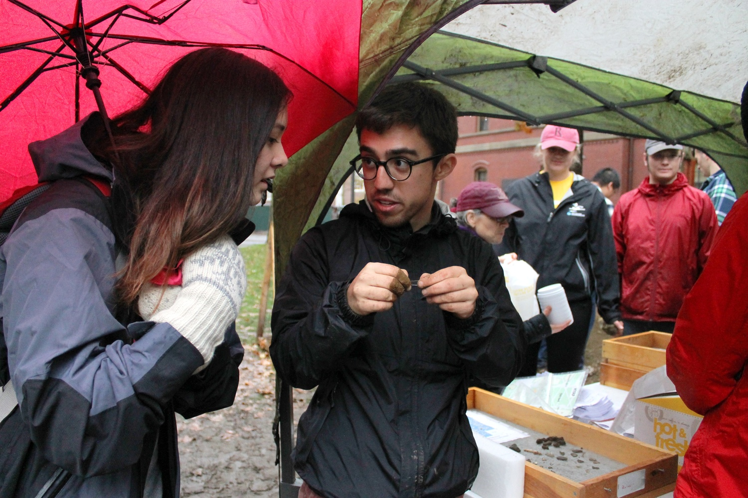 Santiago Pardo '16, member of the Harvard Yard Archaeology Project, explains recent finds to Hannah K. Rasmussen '16 outside of Matthews Hall despite the rain and cold weather on Thursday afternoon.