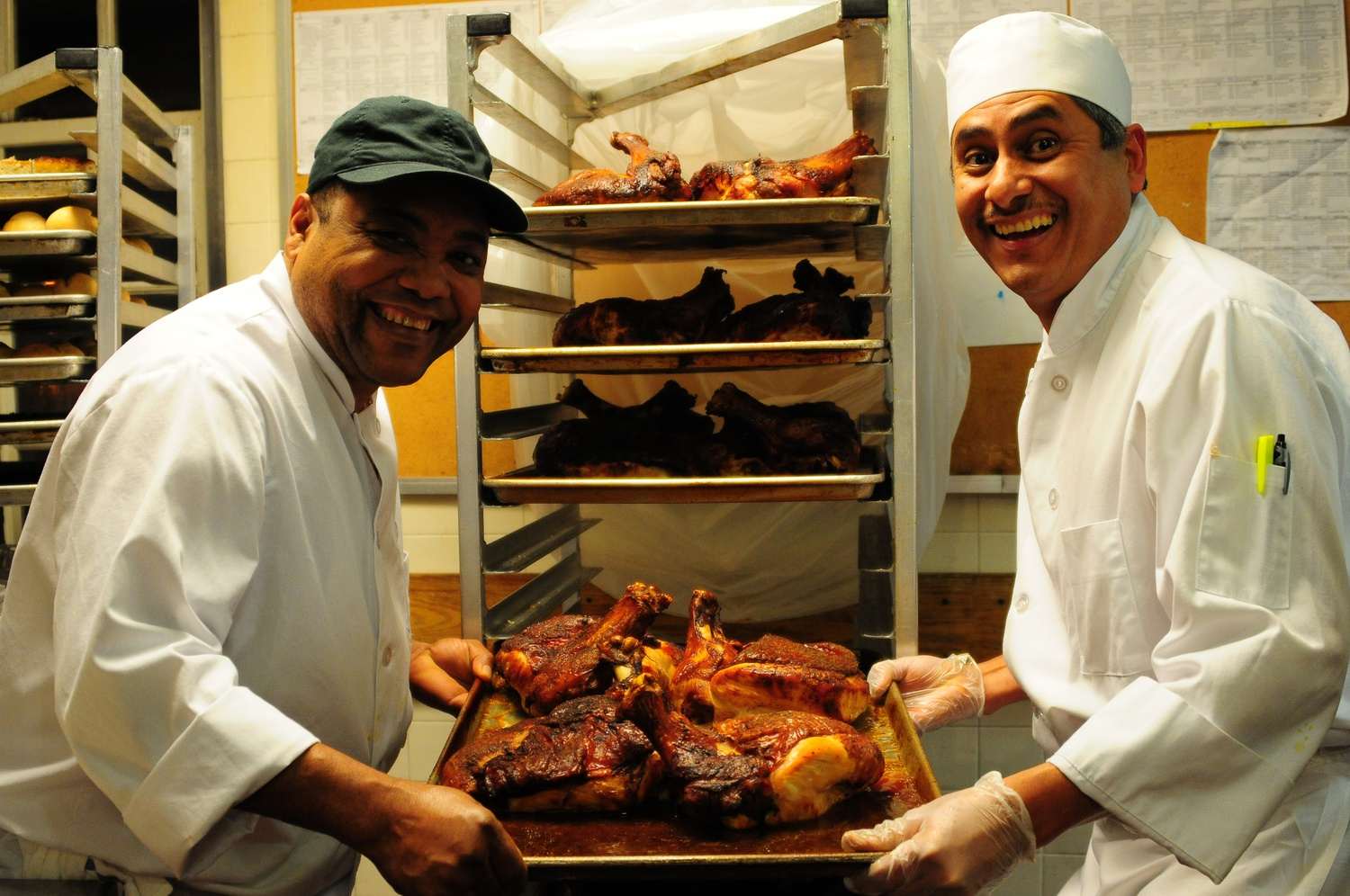 Kirkland Chefs Franklin Espinal and Luis Olmebo display their prepared turkeys for Thursday night's Thanksgiving dinner special.