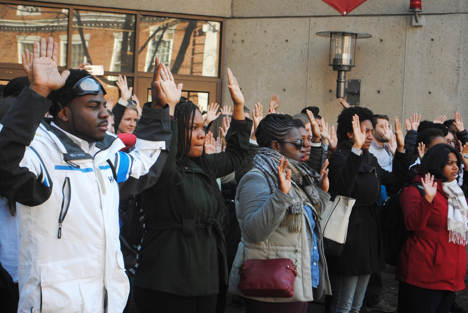"""Protestors with their hands up in deference to the chant """"Hands up, don't shoot."""" Students gathered from the Graduate School of Education to march from Gutmann Library to the Law School on Monday at noon."""