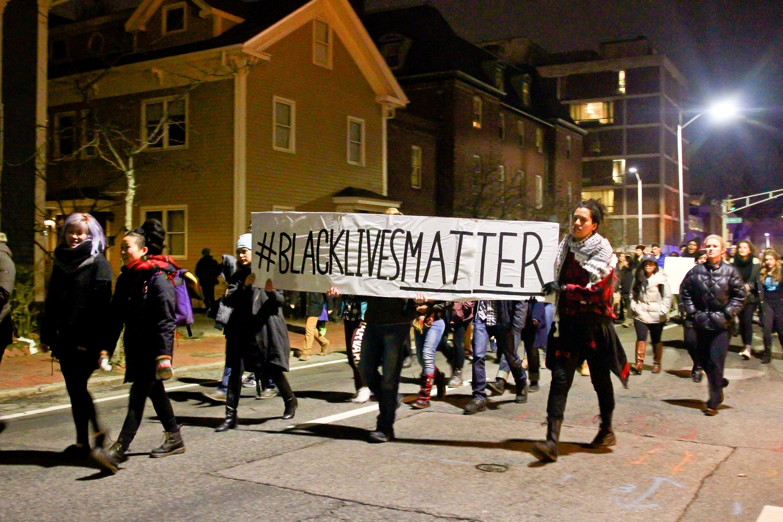 Protestors march down Mt. Auburn street towards Central Square.