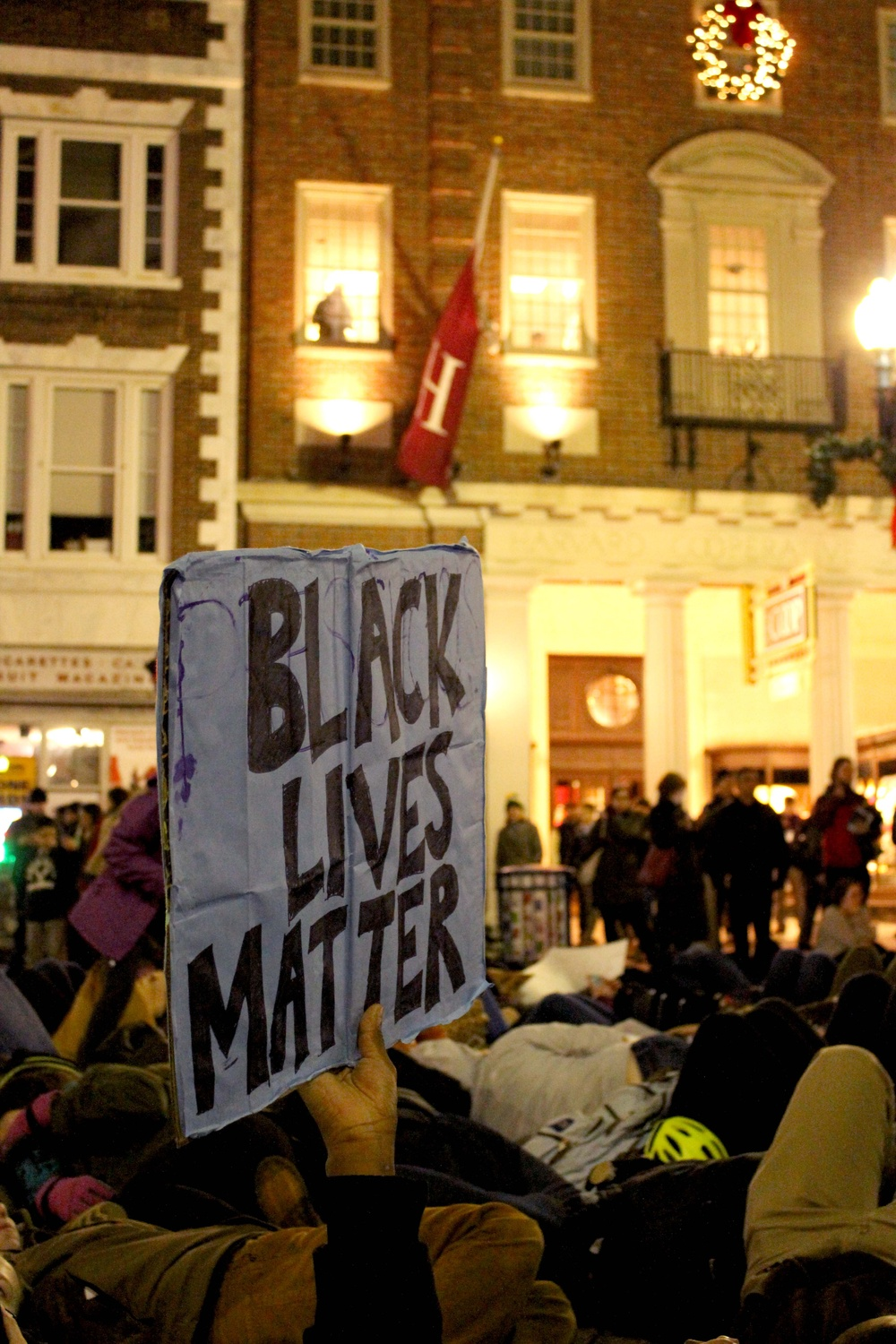 """A protester holds up a sign that reads """"Black Lives Matter"""" during a """"die-in"""" in Harvard Square on Friday evening to protest the recent non-indictments of the officers in the Michael Brown and Eric Garner cases. Protesters began in Davis Square and continued to MIT, laying down at key transportation sites."""