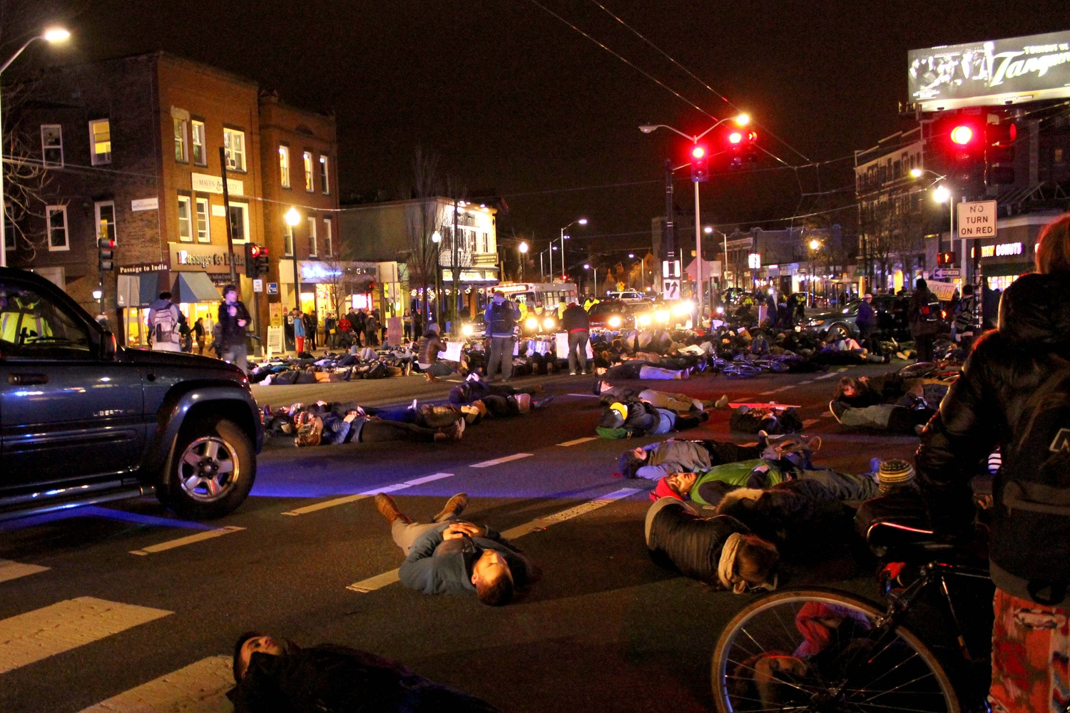 """Protestors lay on Massachusetts Ave. during a """"die-in"""" in Porter Square on Friday evening to protest the recent non-indictments of the officers in the Michael Brown and Eric Garner cases. Protestors began in Davis Square and continued to MIT, laying down at key transportation sites."""
