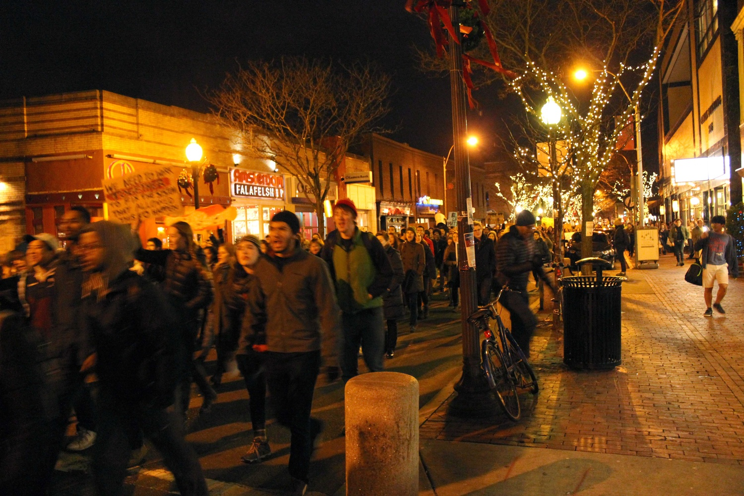 Protestors march from Davis Square to Porter Square on Friday evening in response to the recent non-indictments of the officers in the Michael Brown and Eric Garner cases. Protestors began in Davis Square and continued to MIT, laying down at key transportation sites.
