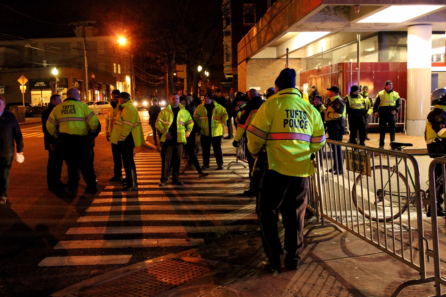 Tufts Police stand near the Davis Square T Station on Friday evening during protests of the recent non-indictments of the officers in the Michael Brown and Eric Garner cases. Protestors began in Davis Square and continued to MIT, laying down at key transportation sites.