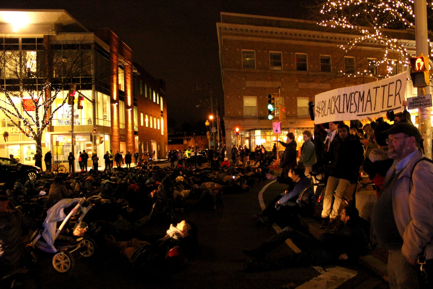 """Protestors lay down during a """"die-in"""" in Davis Square on Friday evening to protest the recent non-indictments of the officers in the Michael Brown and Eric Garner cases. Protestors began in Davis Square and continued to MIT, laying down at key transportation sites."""