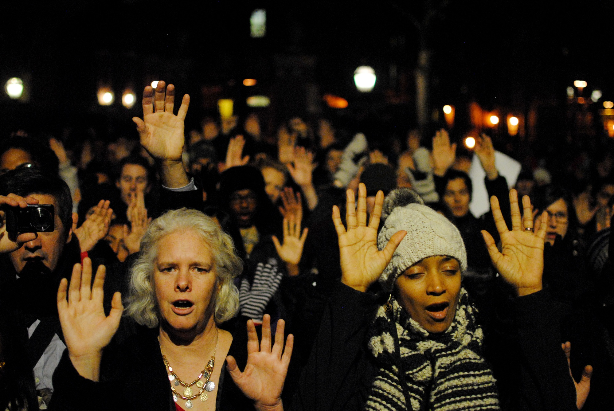"""Members of the Harvard community chant """"hands up don't shoot,"""" at a peaceful protest in the Science Center Plaza in December. The protest brought together students from many Harvard University schools."""