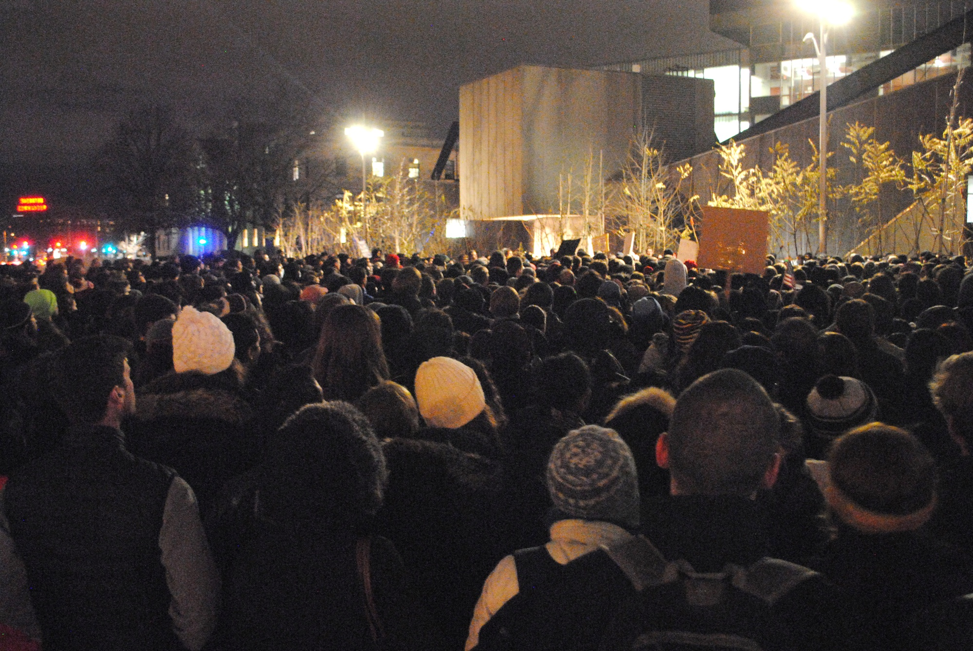 """Hundreds of Harvard affiliates rally in the Science Center Plaza Friday evening for the """"March on Harvard,"""" demonstration."""