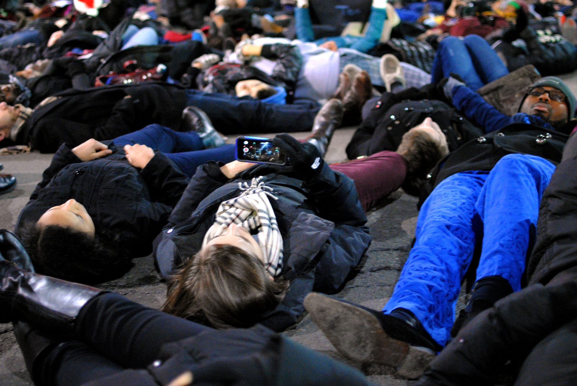 A protestor takes a photo during a die-in in Central Square on Friday evening as a part of the 'March on Harvard' protest.
