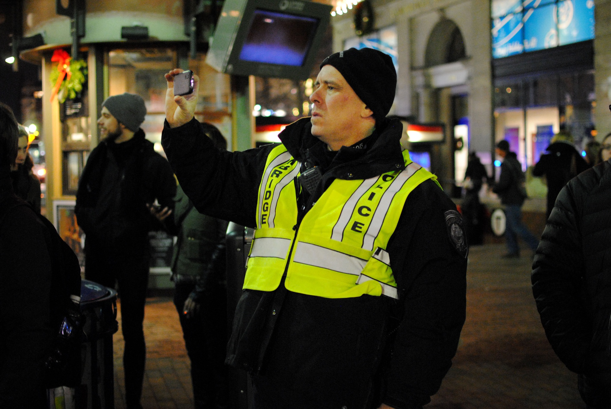 A Cambridge Police officer takes a photograph on his cellphone during a 'die in' in Harvard Square on Friday evening.