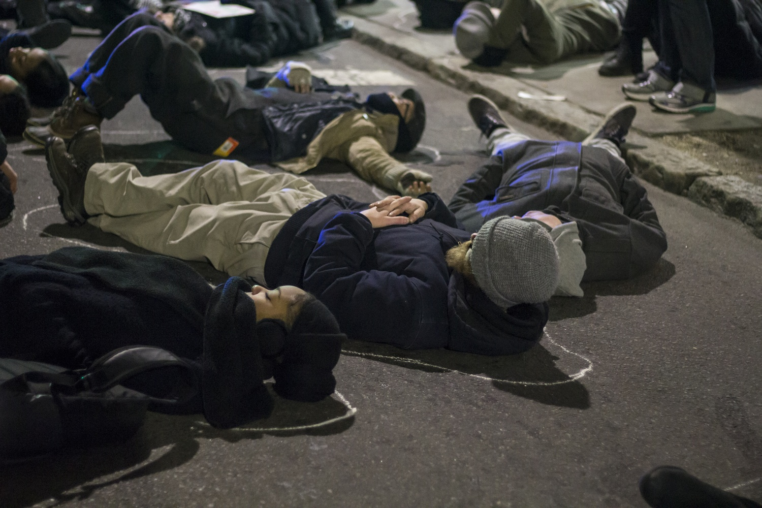 Protest participants lay in the street after having chalk outlines drawn around their bodies during a second die-in during a protest in Cambridge on Wednesday evening. The chalk alludes to the outline law enforcement officers traced around Michael Brown's body.