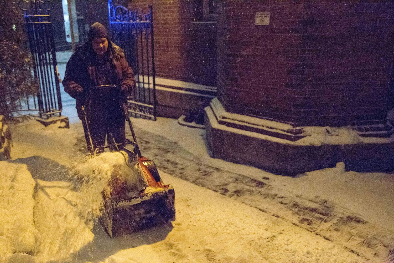 Harvard Campus Services custodian Ramon Casas plows snow outside Adams House on Monday evening. He will spend Monday night on campus with other staff members as a blizzard descends on the Boston area.