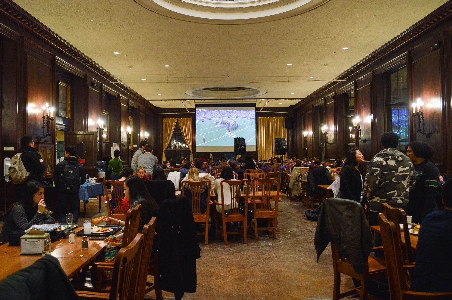 A screen in the back of the Adams House dining hall displays a live screening of the 49th Super Bowl as Adams residents settle for dinner.