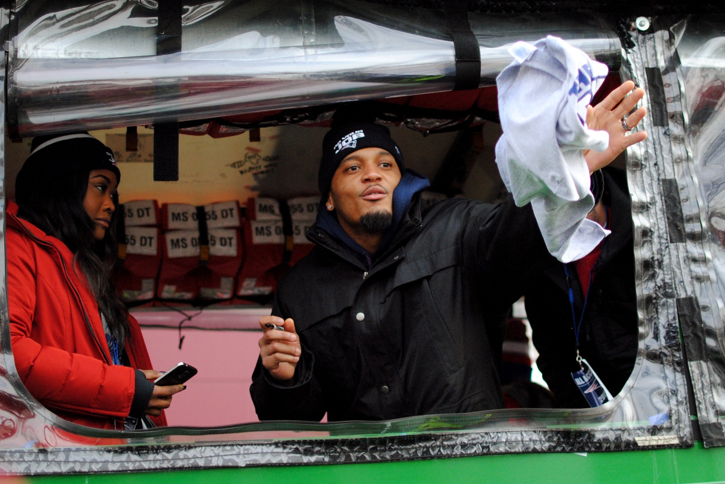 Patrick C. Chung, a strong safety for the Patriots, throws an autographed shirt back to a  fan during the Super Bowl parade in Boston on Wednesday.