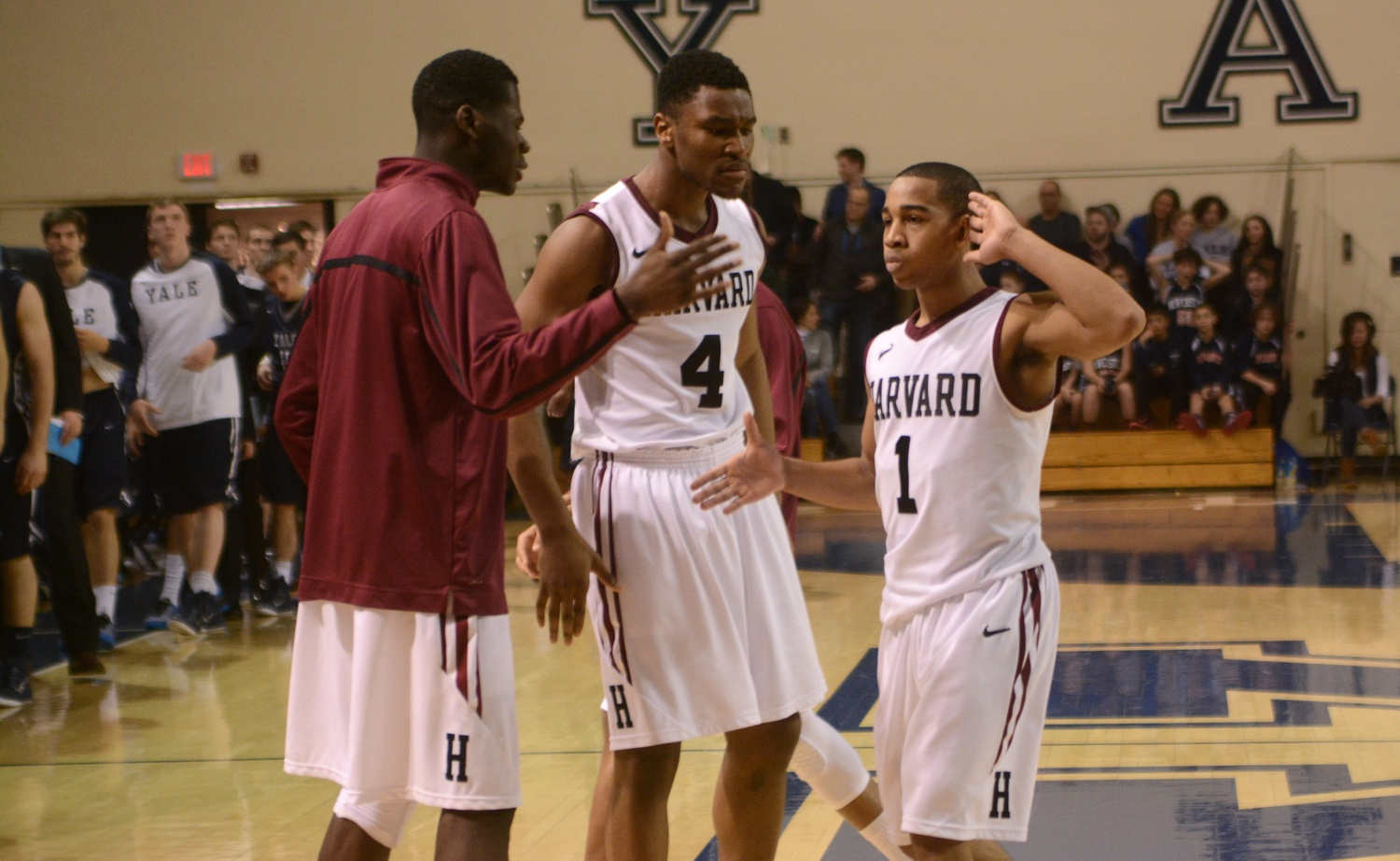 Chris E. Egi '18, left, celebrates with teammates Siyani T. Chambers '16 and Zena Edosomwan '17 after a win over Yale in 2015.
