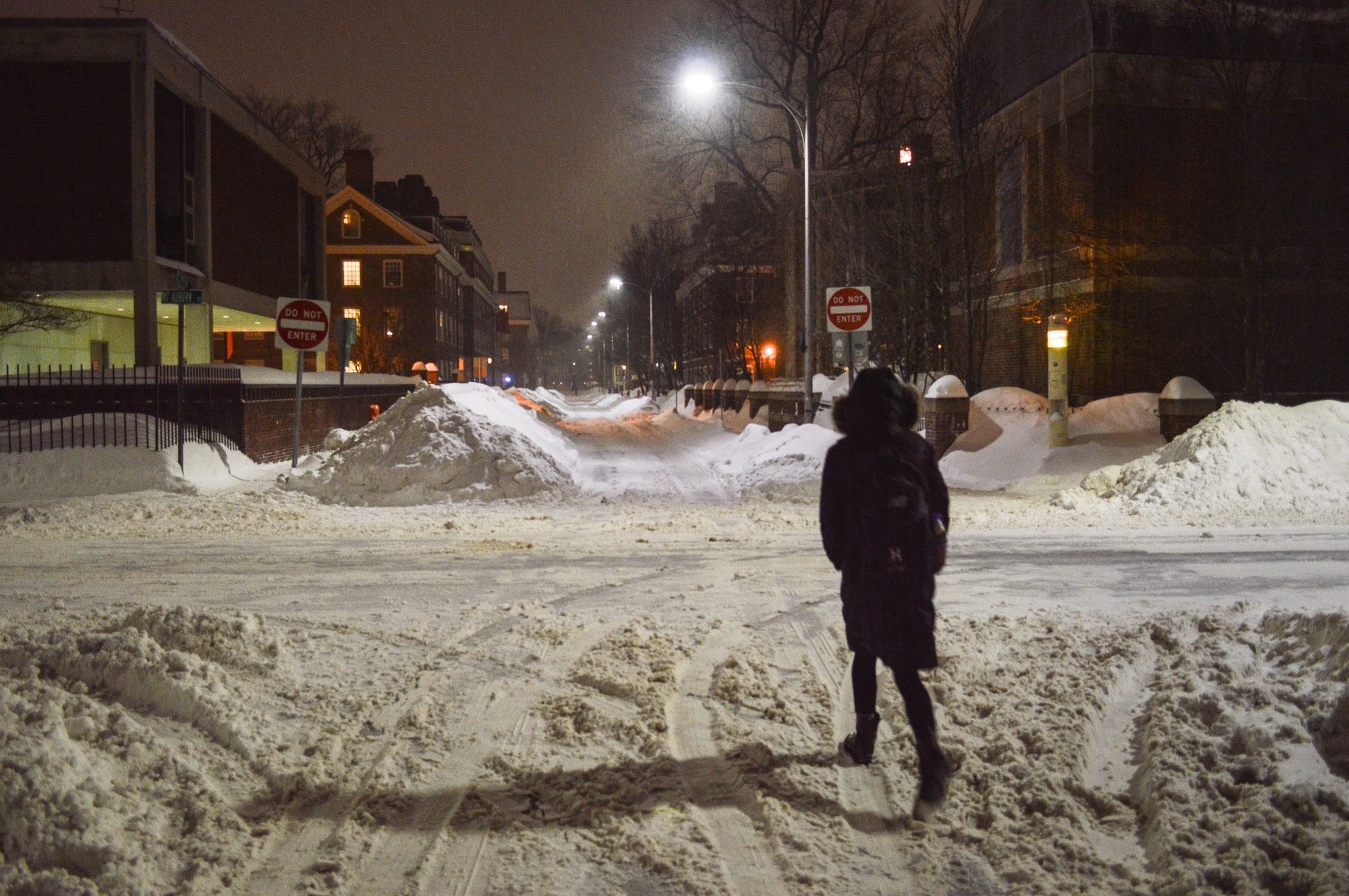 A student walks down Plympton St. on Monday evening, flanked by growing piles of snow. Amid forecasts of more wintry weather, administrators made the decision to suspend most operations at the University on Tuesday.