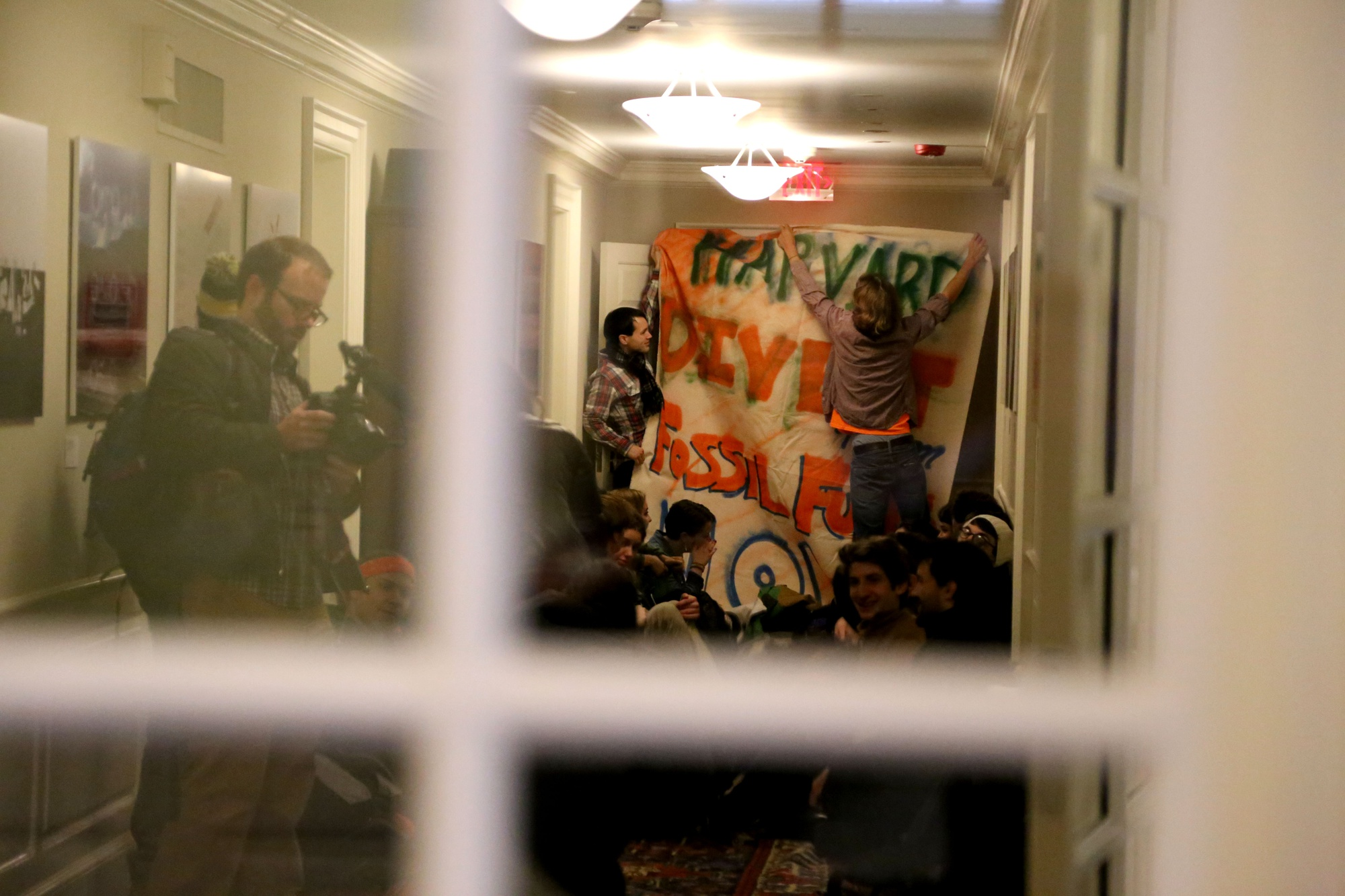Canyon S. Woodward '15 of Divest Harvard hangs a banner during a protest in Massachusetts Hall. A group of students rushed into the building that houses the University president's office this morning.