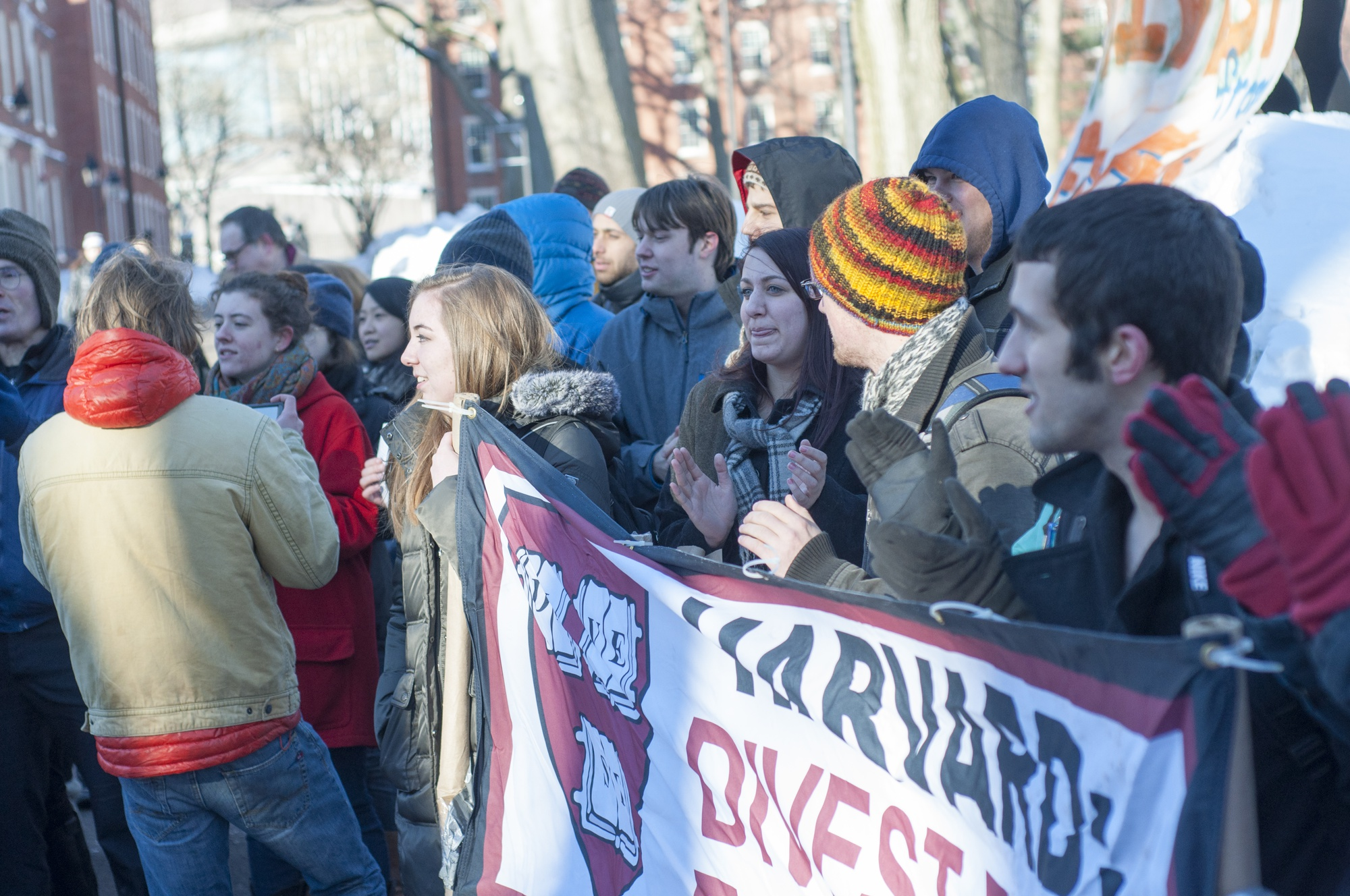 Divest Harvard students held a sign outside Massachusetts Hall on Friday, Feb. 13 as part of Global Divestment Day.
