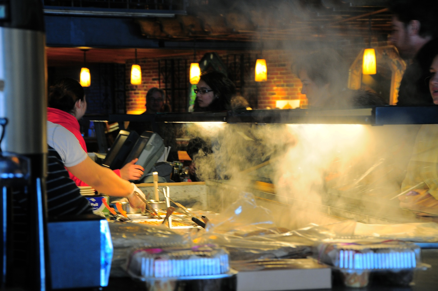 Smoke rises as employees at Felipe's quickly fill burrito orders for customers. Offering a delicious range of Mexican food products such as quesadillas and tacos, Felipe's burritos are one of the most popular items on the menu.