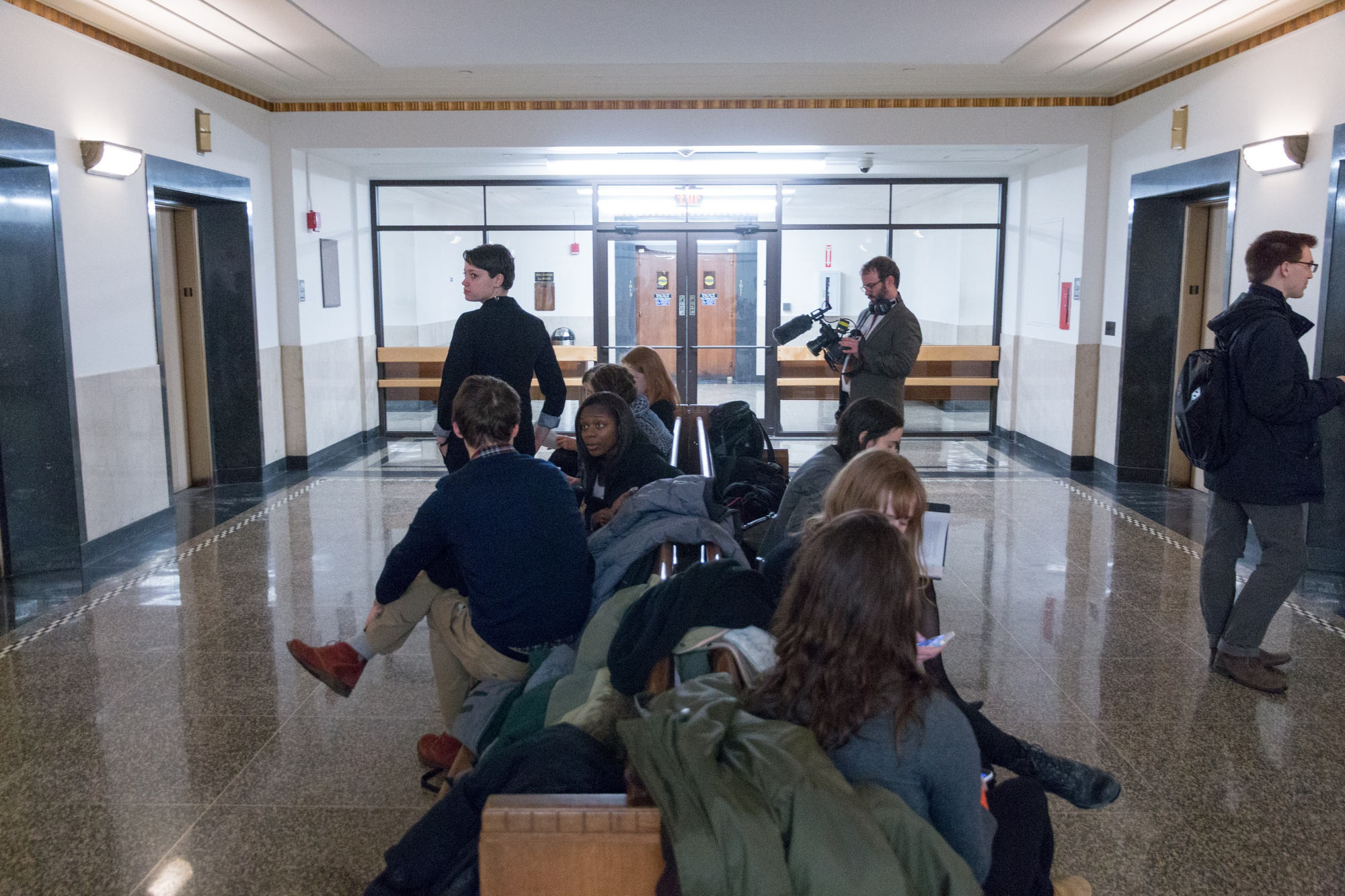 Members of Divest Harvard gather in the elevator lobby just outside a Suffolk County courtroom Friday.