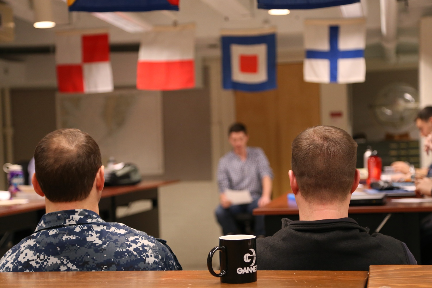 ROTC midshipmen and Marine options give presentations during a naval history class at MIT. Students in Naval ROTC usually take a course on military science each semester.