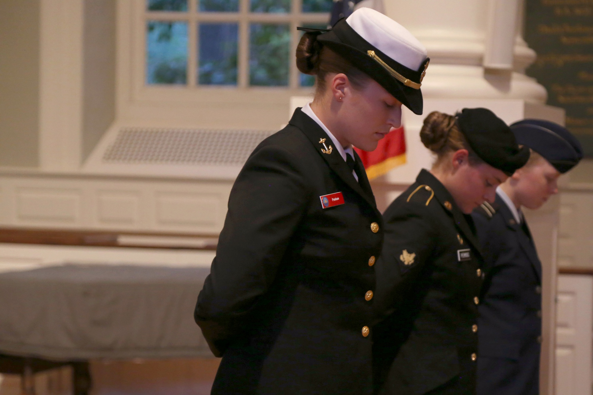 From left, Carolyn F. Pushaw '16, Lucy F. Perkins, and Kira R. Headrick '17 bow their heads during a 9/11 memorial service in 2014.