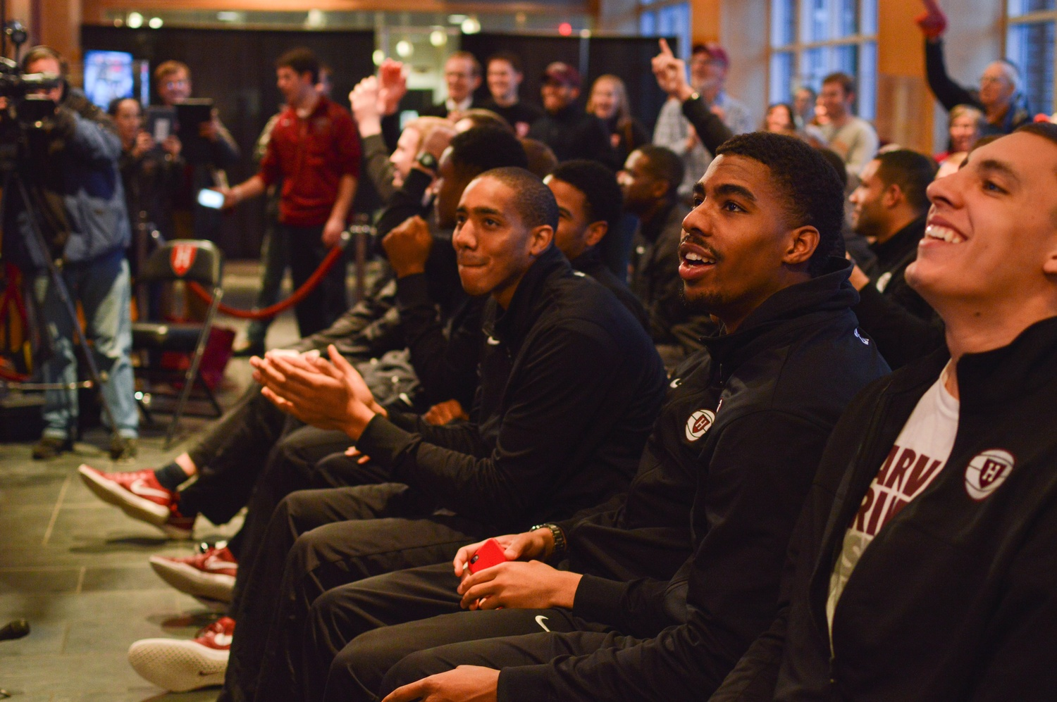 In a crowded Murr Center, players and supporters alike react to a television live-stream of themselves with applause and raised hands. Harvard will face off against North Carolina on Thursday.