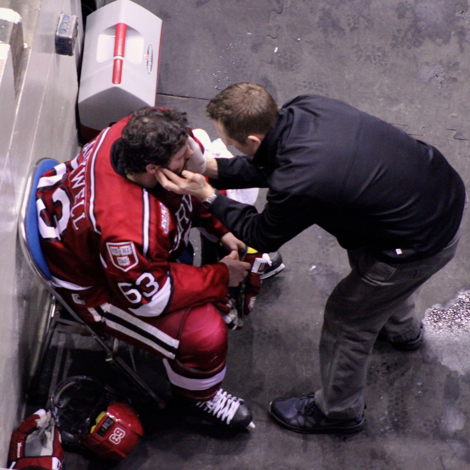 Fourth-year forward Colin Blackwell is evaluated by Harvard trainer Chad Krawiec after a hit by Quinnipiac sophomore Tim Clifton. Clifton was ejected for the play.