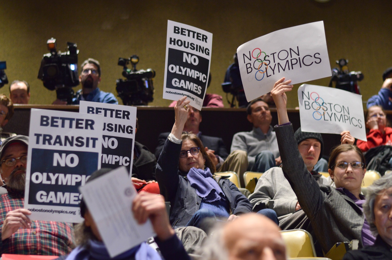 In response to a presentation from representatives of the Boston 2024 Olympic Committee, several members of the audience raise signs opposing the games Tuesday evening. The meeting, held at the Harvard Business School, was one of many planned by Olympic Boston 2024 to solicit community feedback.