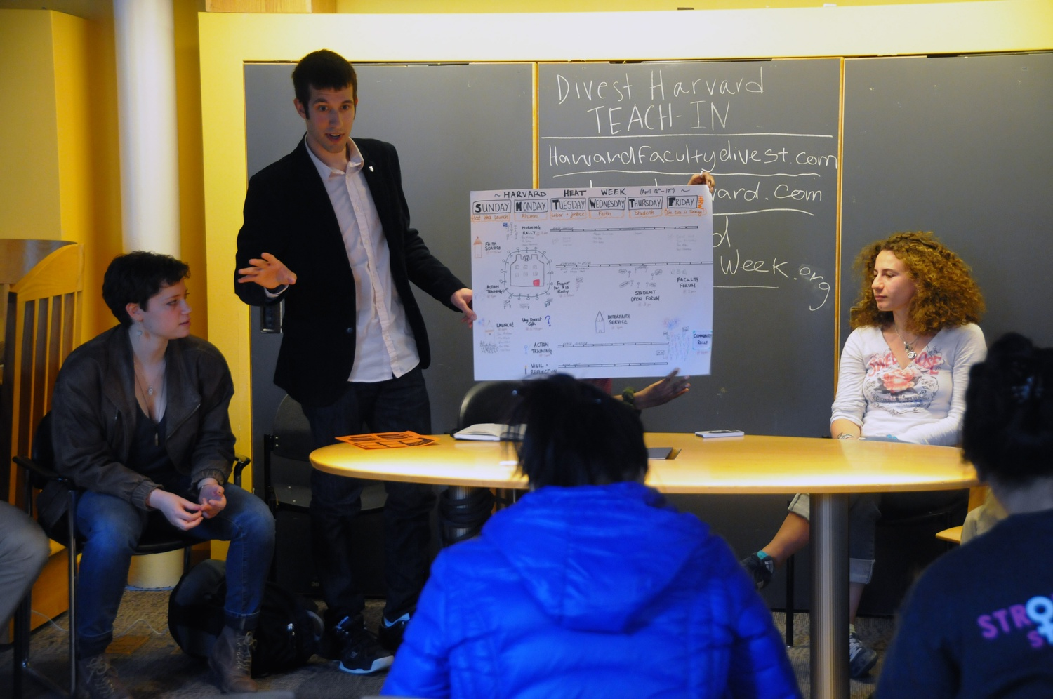Members of Divest Harvard speak about the history of the group, which began with three students and has held active peaceful protests, fasts, and sit-ins since its conception three years ago in Ticknor Lounge on Monday evening.