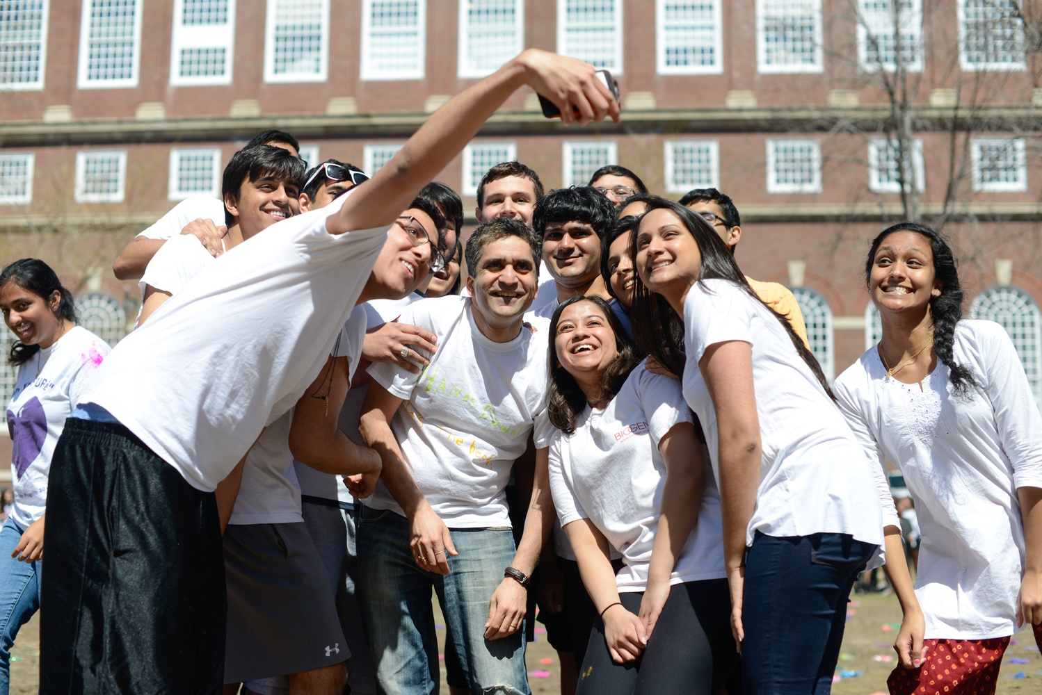 Dean of College Rakesh Khurana takes a selfie with a group of students at an event celebrating Holi on Sunday.