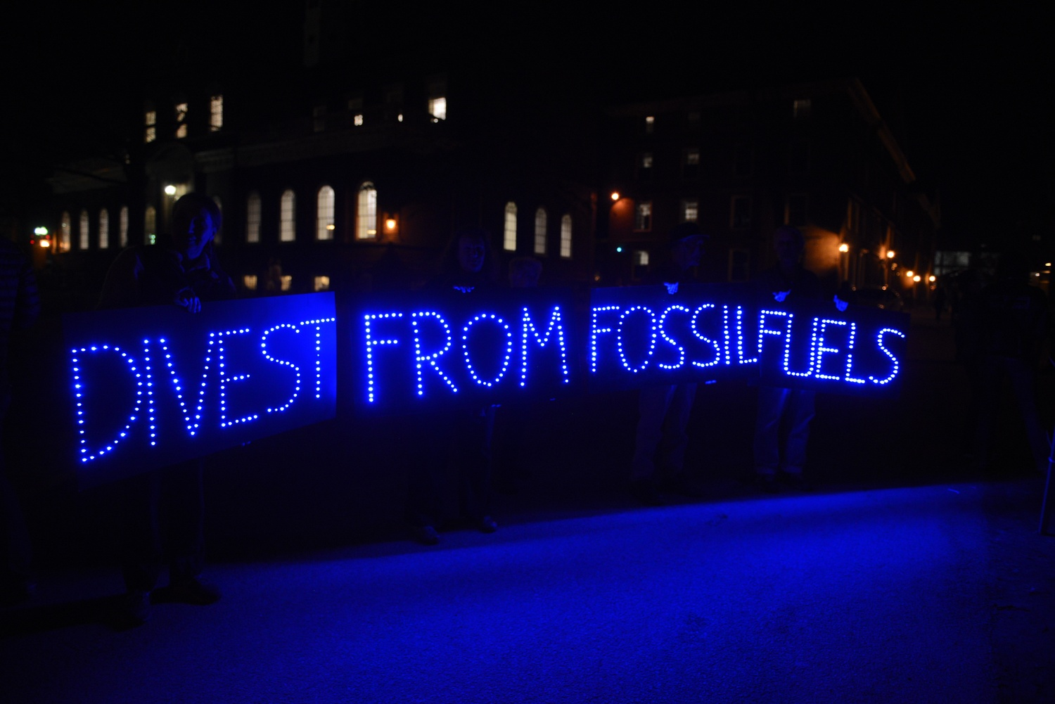 Members and supporters of activist group Divest Harvard hold signs and banners in front of Massachusetts Hall on Sunday night. The group says it plans to blockade the administrative building until Friday.