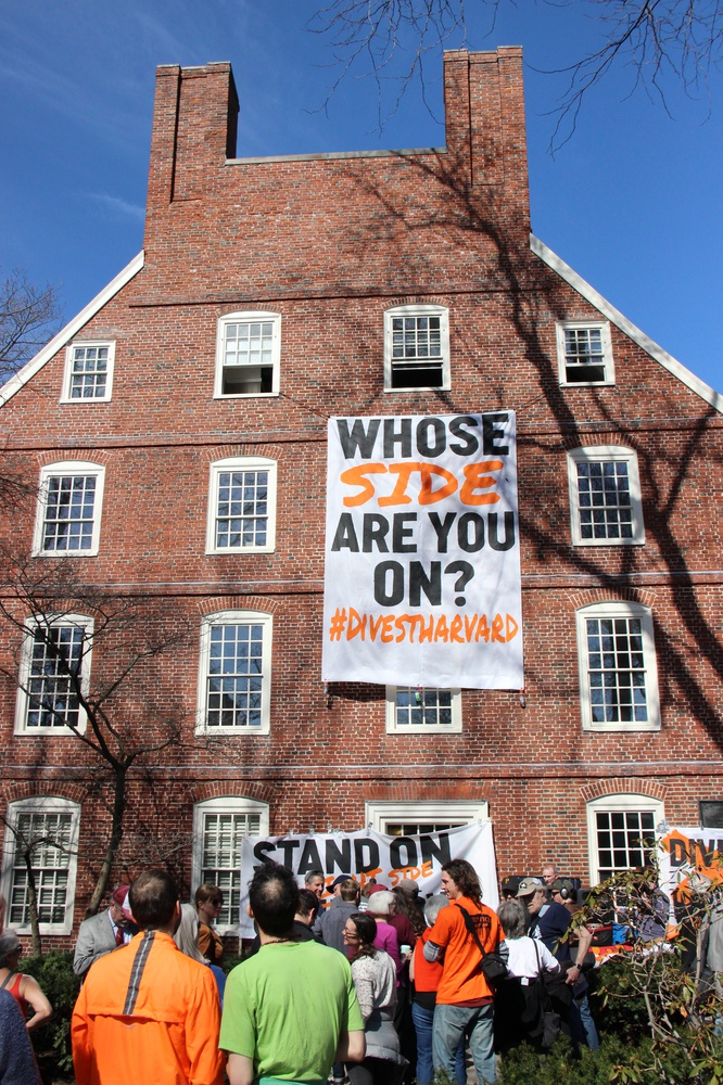 """Protesters hang a banner from the upper floors of Massachusetts Hall. They held a kickoff rally Monday morning as part of """"Harvard Heat Week."""""""
