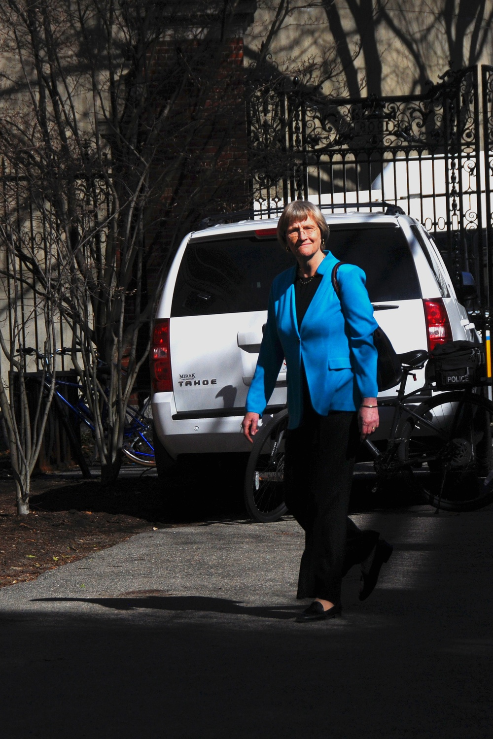 University President Drew G. Faust enters Emerson Hall, where members of the student activist group Divest Harvard attempted to confront her before she introduced a lecture on Wednesday afternoon. Security personnel had  placed guard rails between Loeb House and the lecture hall.