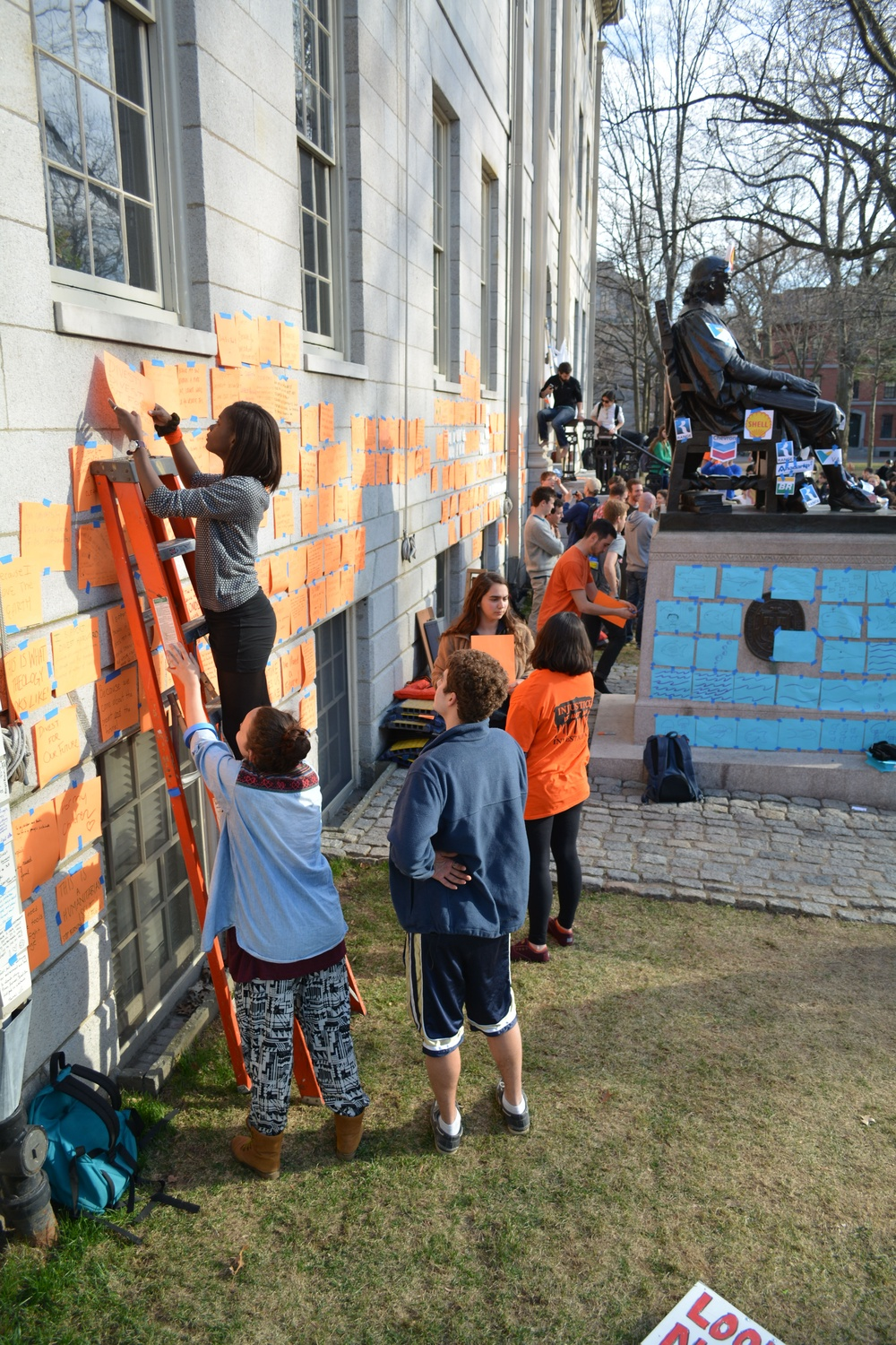 While other protesters lined up along the perimeter of University Hall, a student hangs up messages supporting the Divest movement written on orange sheets of paper. In the background, pictures of oil company logos are taped on the statue of John Harvard.