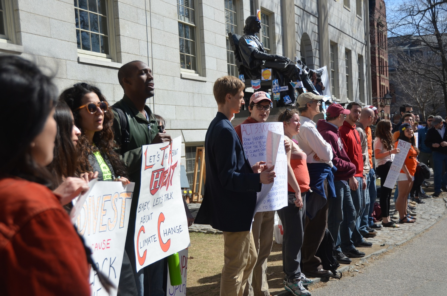 Divest protestors line up around University Hall on Thursday afternoon as part of Harvard Heat Week.
