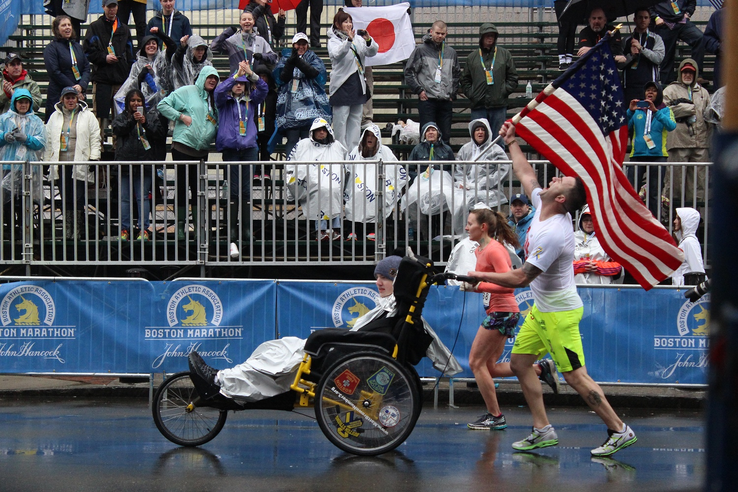 Former Army Ranger Lucas Carr, right, and Stonehill College student Matt Brown, who has been a quadriplegic since he was 15, celebrate as they near the end of the race. The two have run multiple marathons together for charity since 2012.