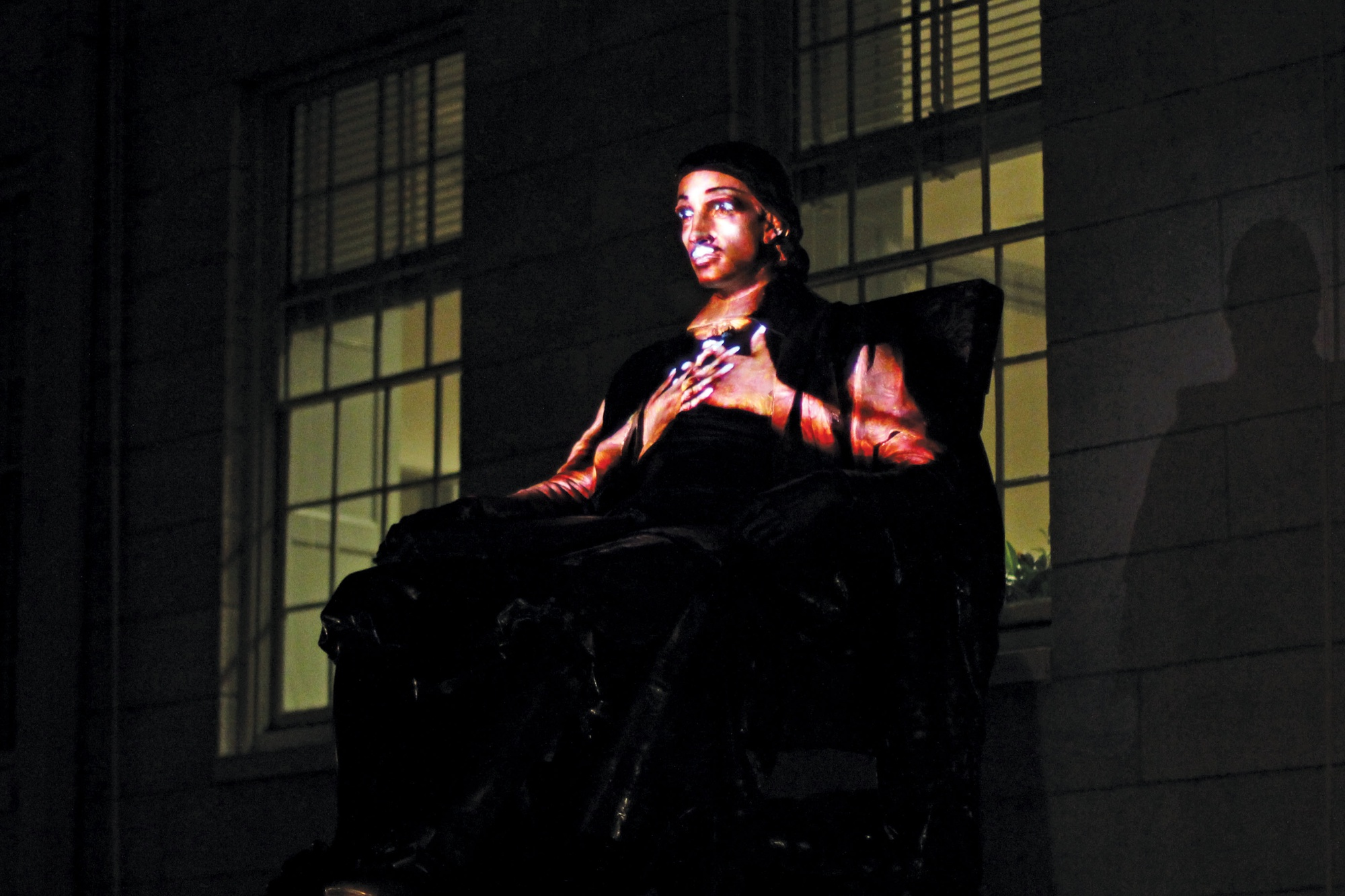 Artist Krzysztof Wodiczko projects recorded videos of students on the John Harvard statue Tuesday night. Wodiczko used the statue as a medium through which to voice concerns about job security and fears about not being able to make a difference in the world, while drawing upon themes of loneliness and disconnection.