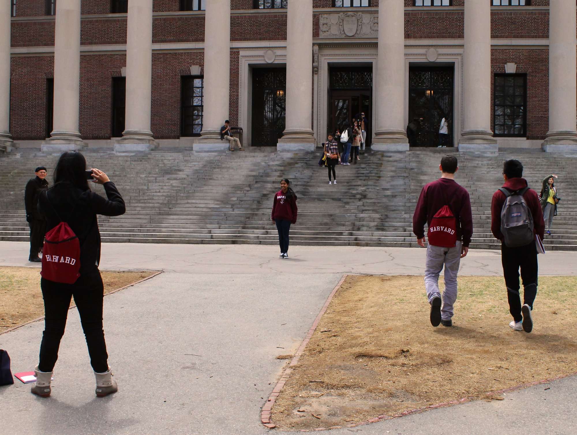 """Prefrosh Saloni Vishwakarma takes a picture of fellow prefrosh Deepika S. Kurup in front of Widener Library on Monday, the last day of Visitas. """"Visitas has been phenomenal. One of the best parts is how approachable everyone is,"""" said Kurup."""