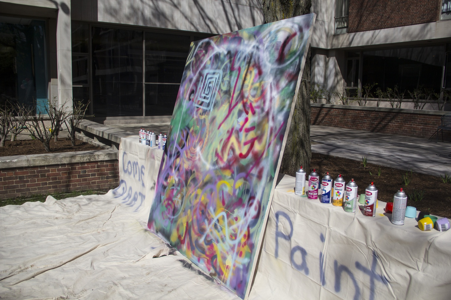 Students used spray paints to color a canvas in Quincy courtyard as part of an Interactive Art in the Courtyard event in the house.