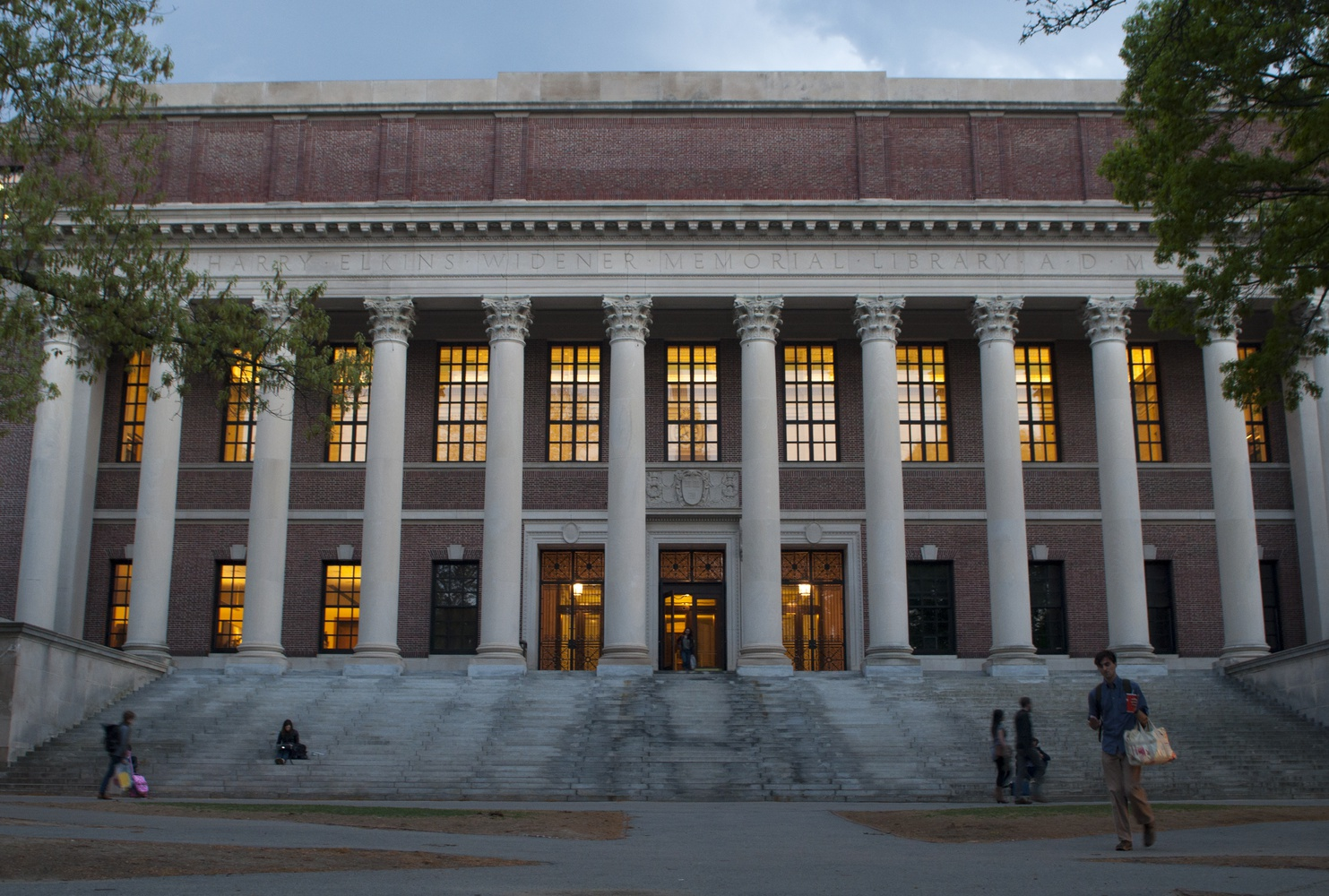 Students filter through Widener Library at dusk on Tuesday during exam period.