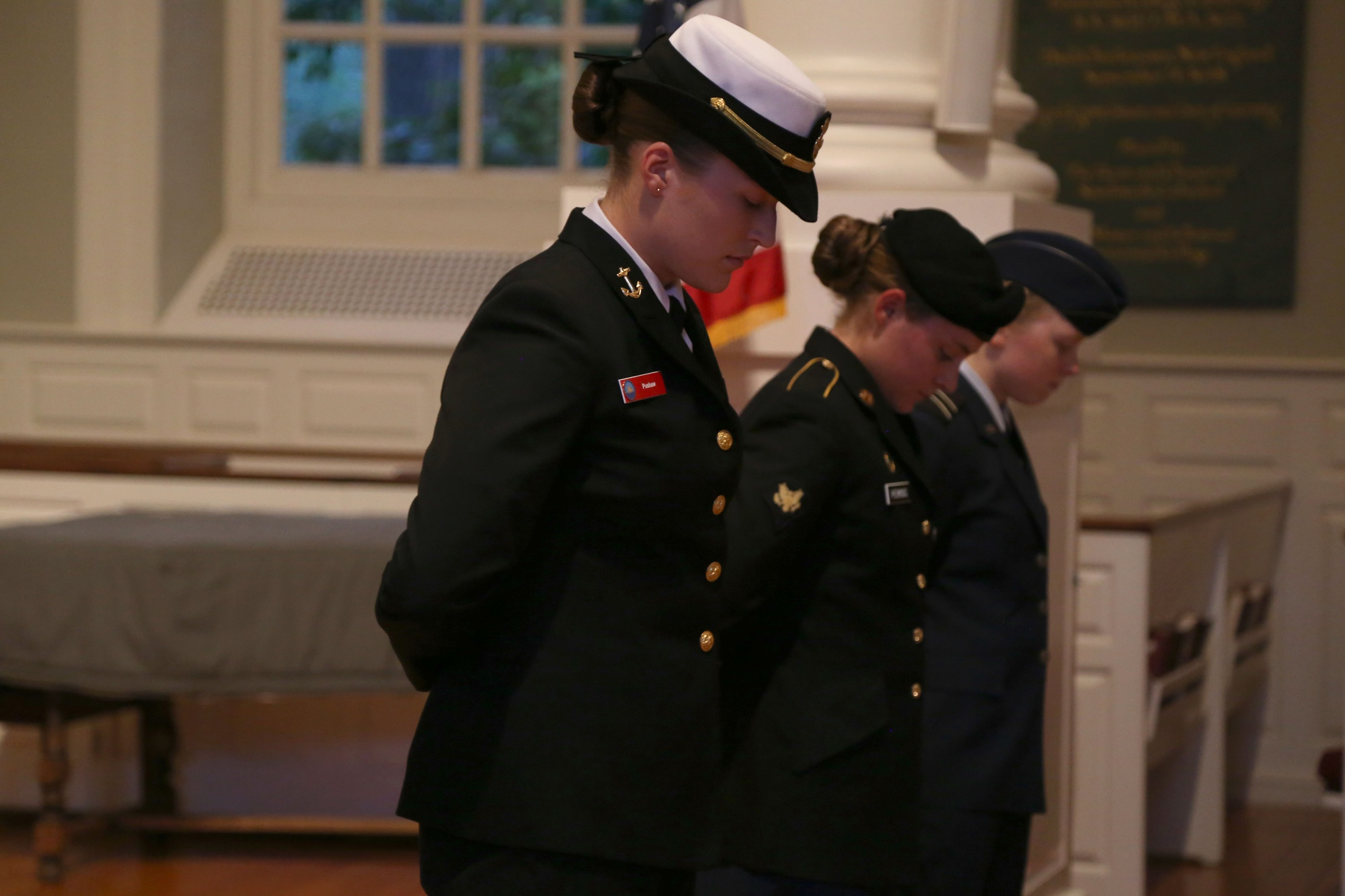 From left, Carolyn F. Pushaw '16, Lucy F. Perkins, and Kira R. Headrick '17 bow their heads during a 9/11 memorial service hosted by ROTC cadets and midshipmen in 2014.