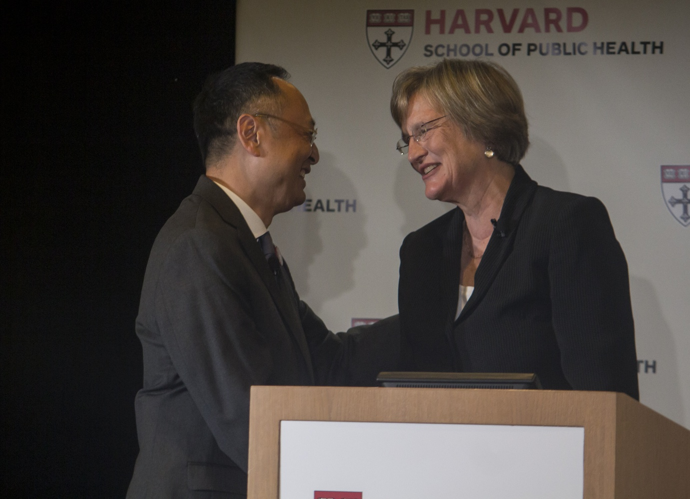 University President Drew G. Faust welcomes Gerald L. Chan  on stage at the unveiling of his foundation's $350 million gift to the Harvard School of Public Health in September 2014.