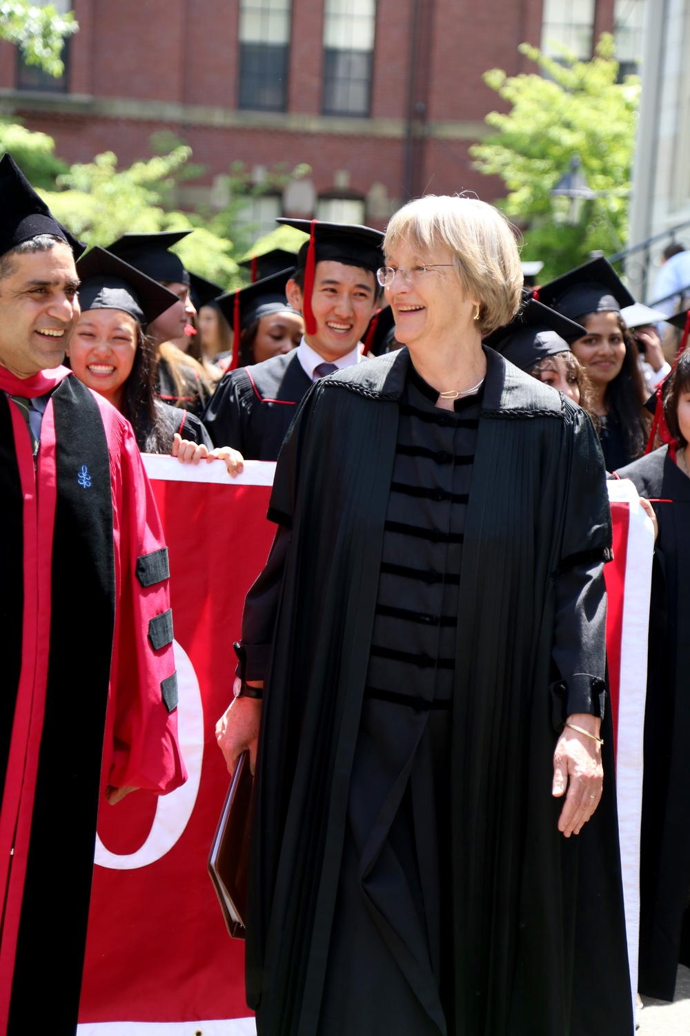 University President Drew G. Faust leads the Class of 2015 in a procession toward Memorial Church for the 2015 Baccalaureate Service on May 26. Dean of the College Rakesh Khurana smiles at left and the 2015 class marshals follow behind.