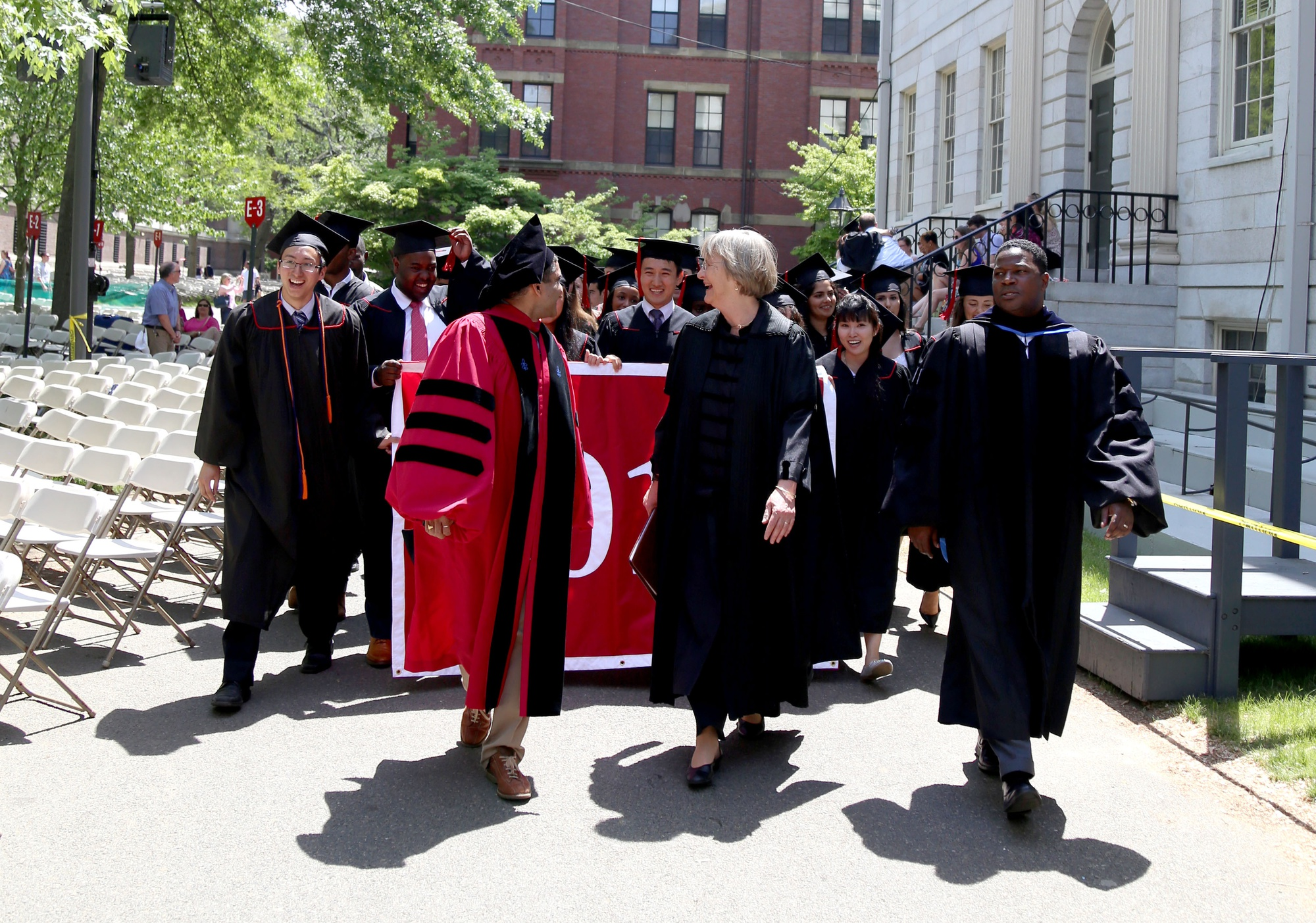 Dean of the College Rakesh Khurana, front left, and University President Drew G. Faust, front center, smile at the 2015 senior class marshals as they lead the Class of 2015 with Reverend Jonathan L. Walton, front right, to Memorial Church for the 2015 Baccalaureate Service on May 26.